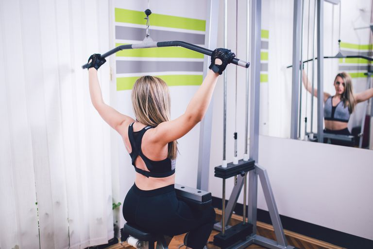 Woman working out on weight lift machine