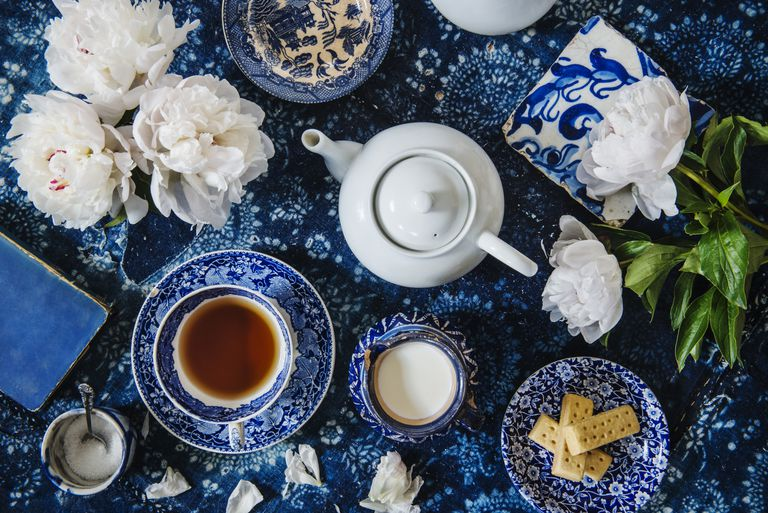 Tea setting with english tea, flowers, biscuits, sugar, books and a tea pot