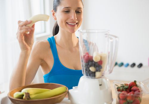 Caucasian woman blending fruit smoothie