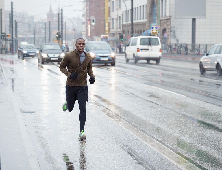 sporty man jogging through rainy city scape