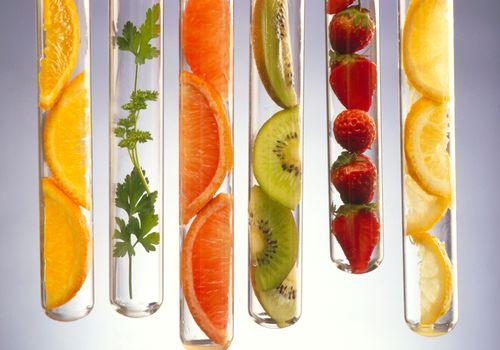 Alimentos ricos en vitamina C presentados en tubos de ensayo.