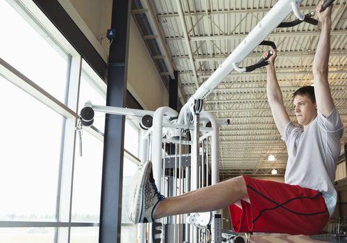 man doing hanging leg raises in gym
