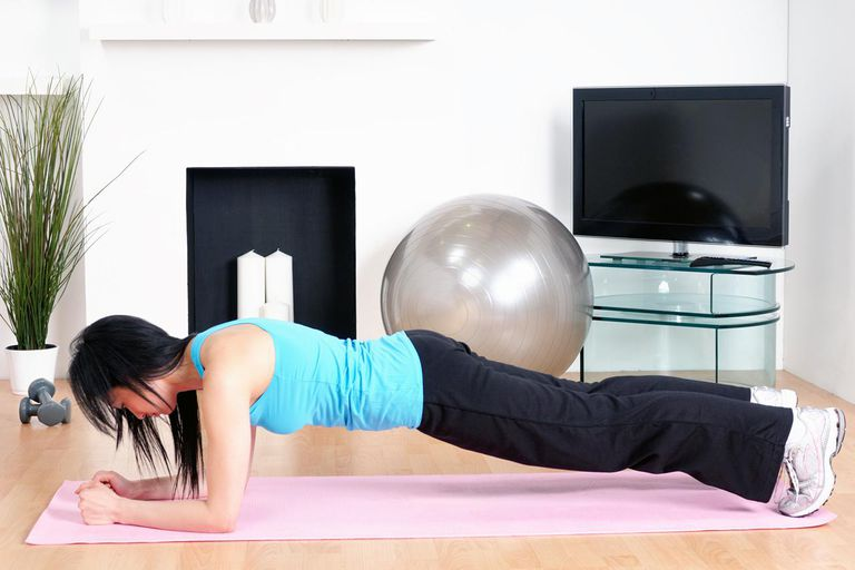 A woman performing a plank exercise in the comfort of her own living room.See more home exercise images here: