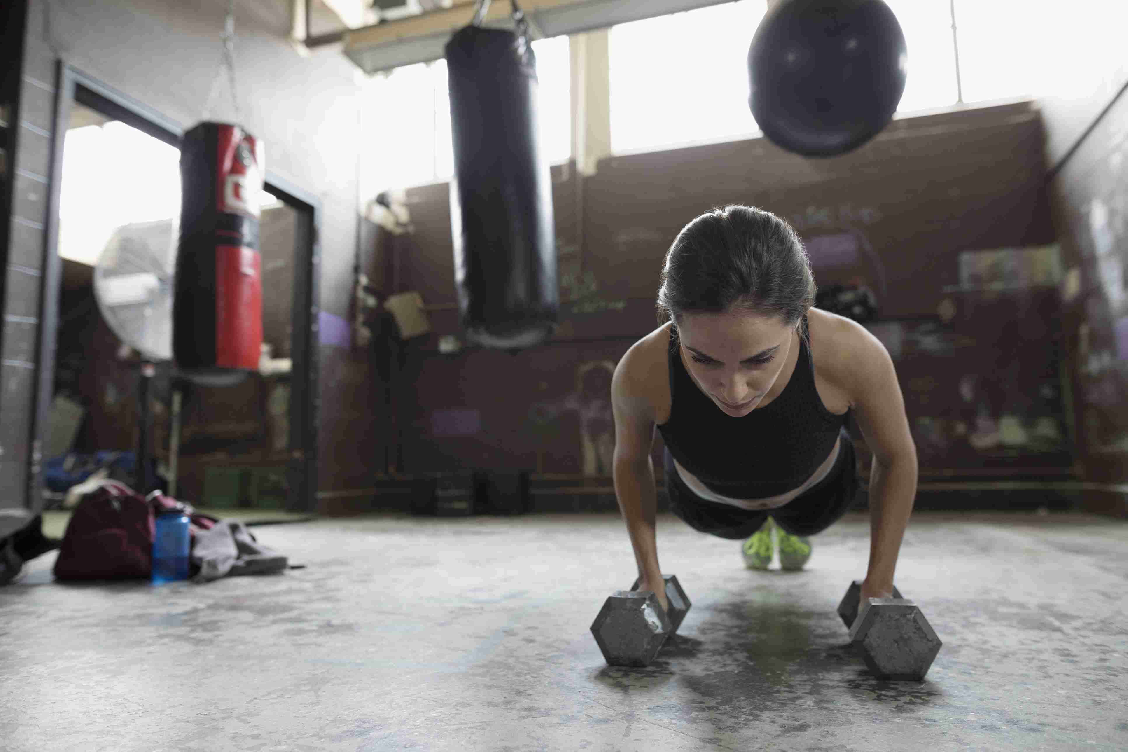 Strong female boxer doing plank exercise with dumbbells at gym