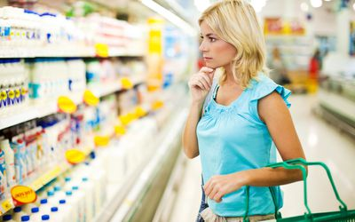 Woman shopping dairy in a food store.