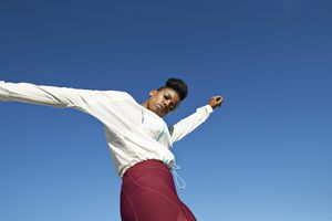 woman wearing workout clothes with a bright blue sky behind her