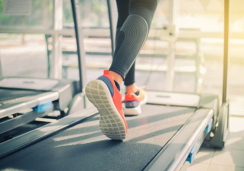 Woman's feet running on treadmill in gym