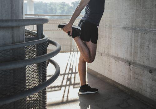 Runner stretching quadriceps to avoid injury