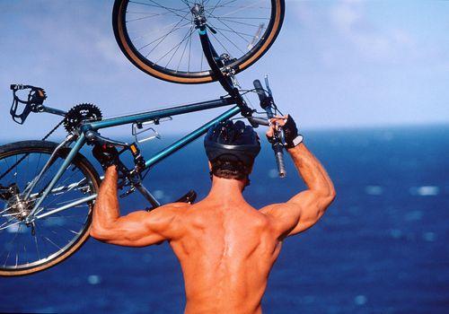 Hombre llevando bicicleta de montaña sobre la cabeza, vista trasera