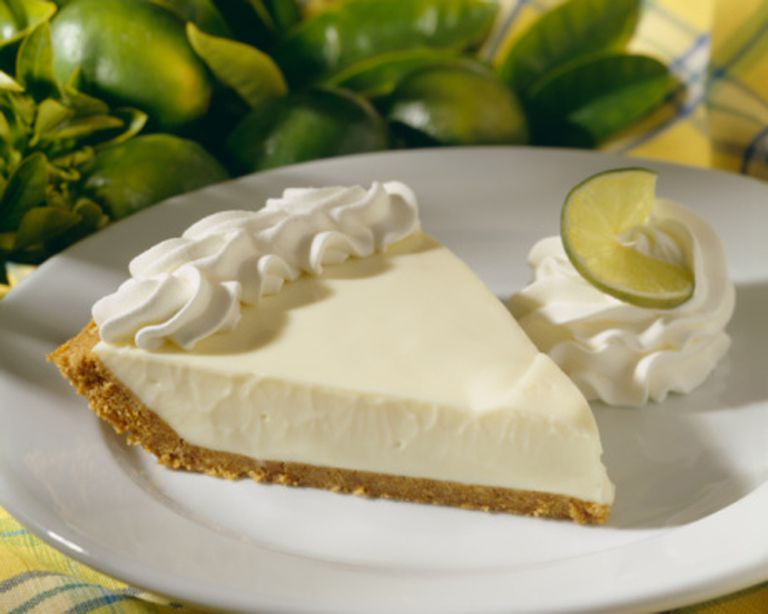 Key lime pie slice topped with whipped cream on white plate