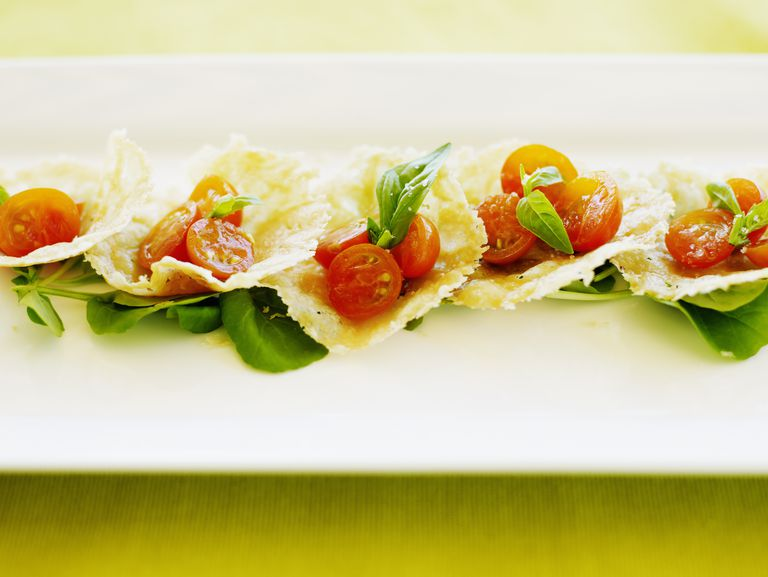 Parmesan crisps with sunburst cherry tomatoes, basil and sea salt, close-up