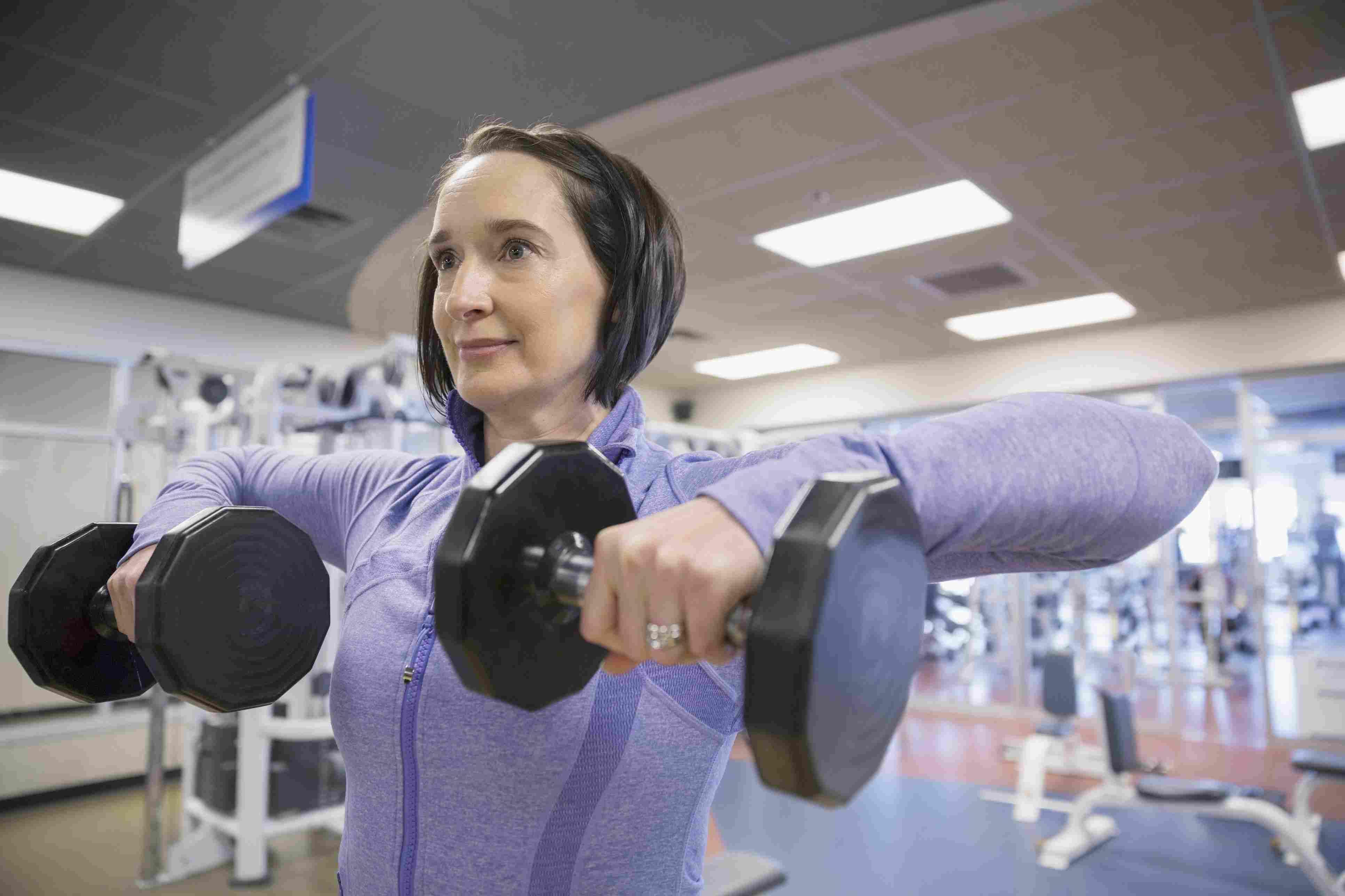 Mujer haciendo trabajo en la parte superior del cuerpo en el gimnasio con pesas