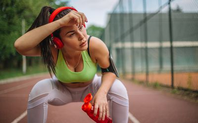 Woman on a track crouching down and holding her head