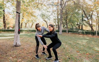 Personal trainer and client exercising outdoors