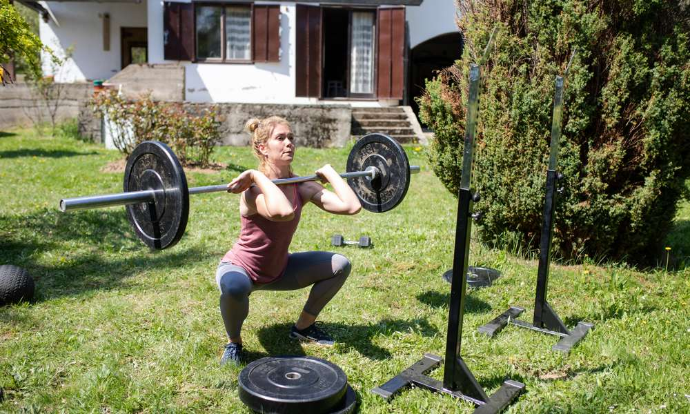 A woman doing weightlifting in her backyard.