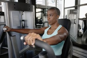 A woman using a chest press machine in a gym