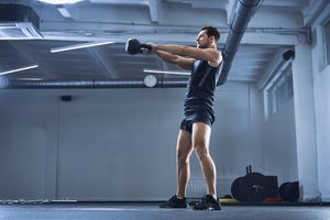 Athletic man doing kettlebell swing exercise at gym