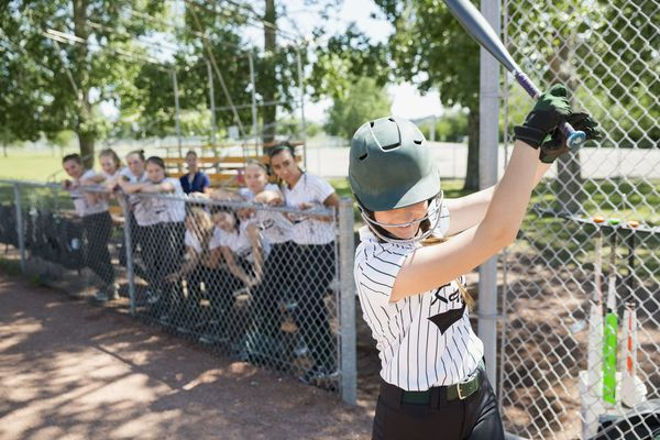 Middle school girl softball player preparing in batter