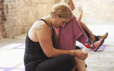 Woman wiping her forehead with a towel in the gym