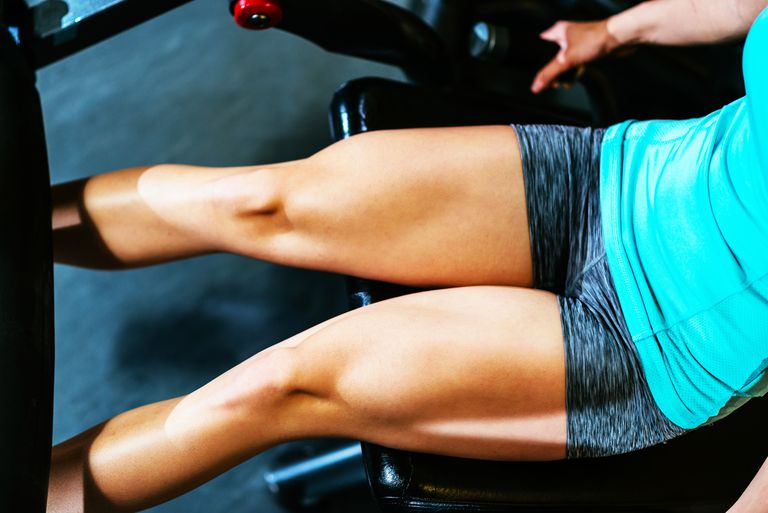 Shot of a woman's quads as she works on a leg extension machine