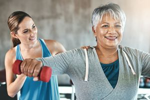 trainer working with mature woman lifting weights