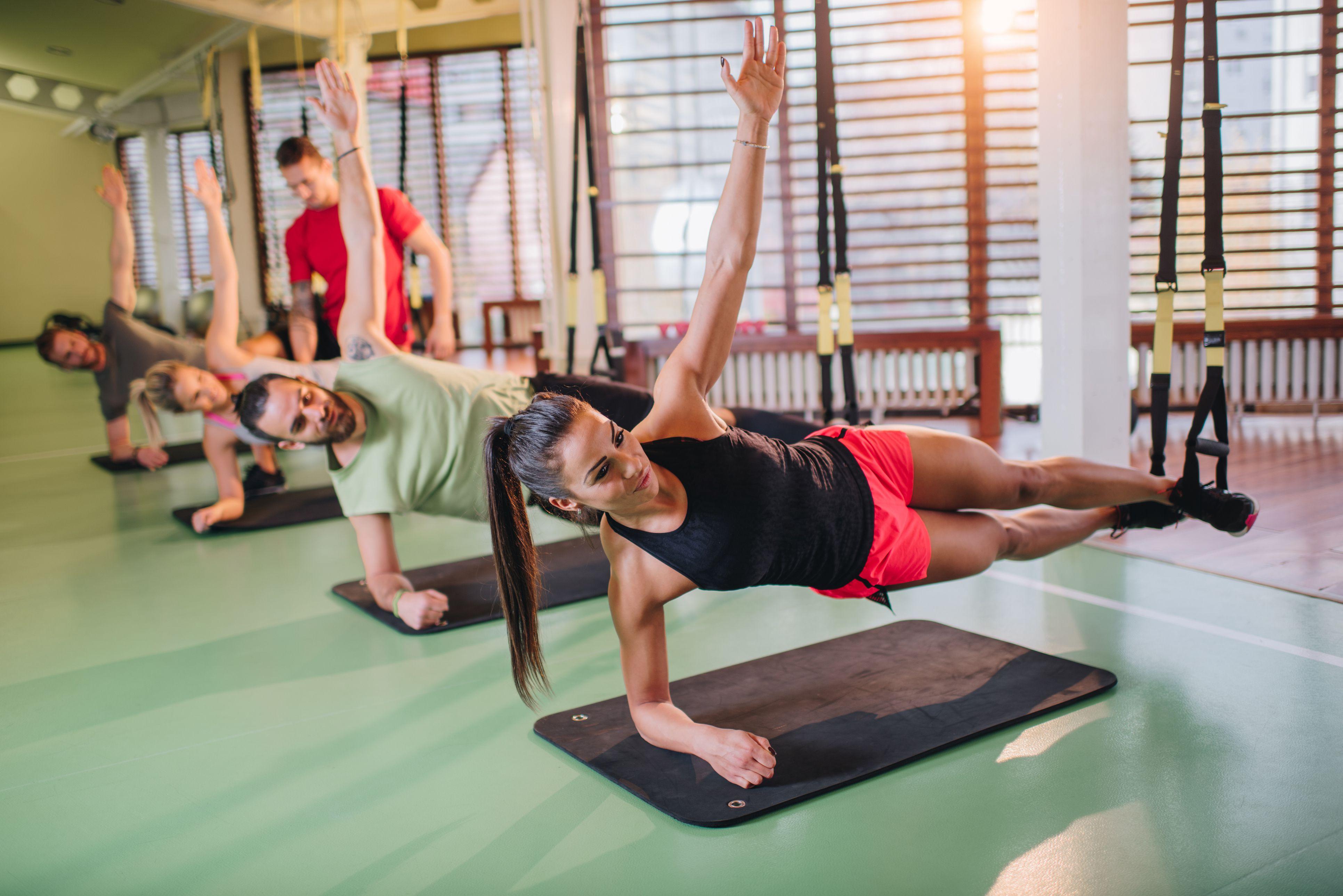 Gente atlética que ejercita el equilibrio en el entrenamiento de suspensión en un gimnasio.