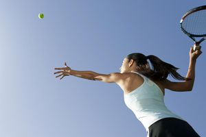 Female tennis player serving ball, low angle view