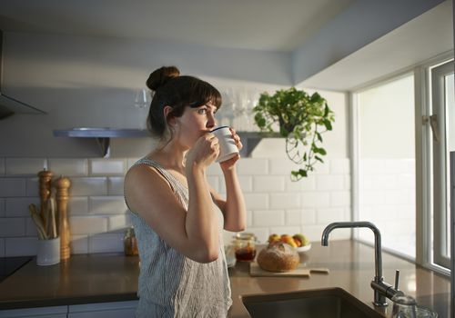 A woman drinks a cup of coffee near a sunny window in her kitchen.