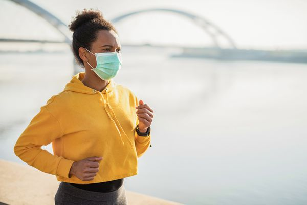 A woman wearing a yellow sweater and a mask jogs along a waterfront during the pandemic.