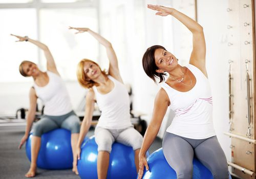 Women sitting on the fitness balls and doing stretching exercises.
