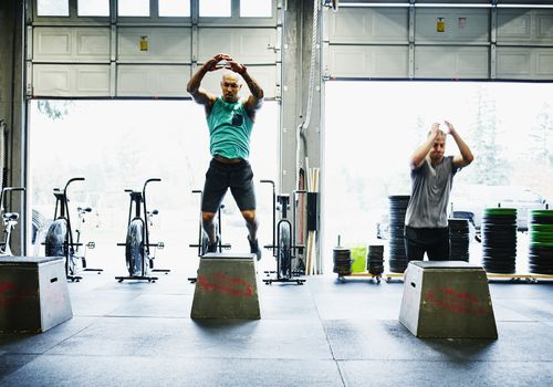 Hombres haciendo saltos de caja en un gimnasio Crossfit
