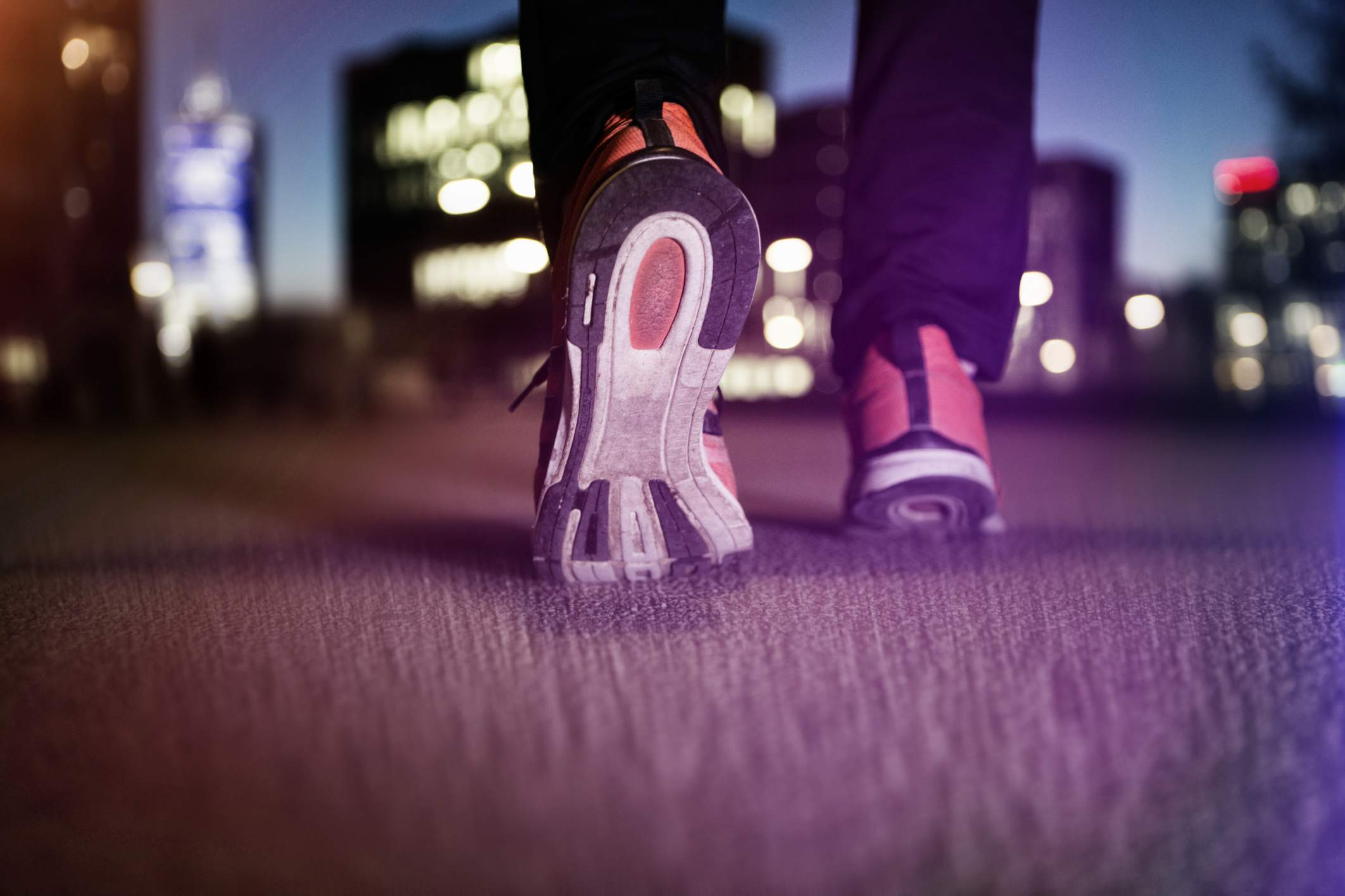 close up sneakers on pavement during nighttime walk