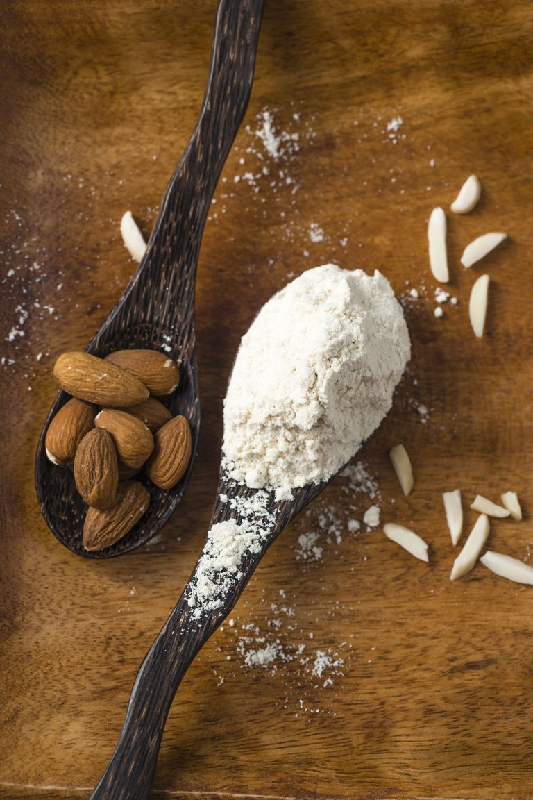 Almond flour and almonds on wooden spoons