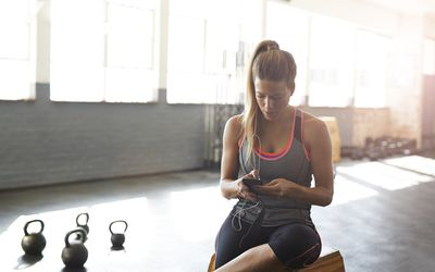 Woman tjecking results on smartphone at gym