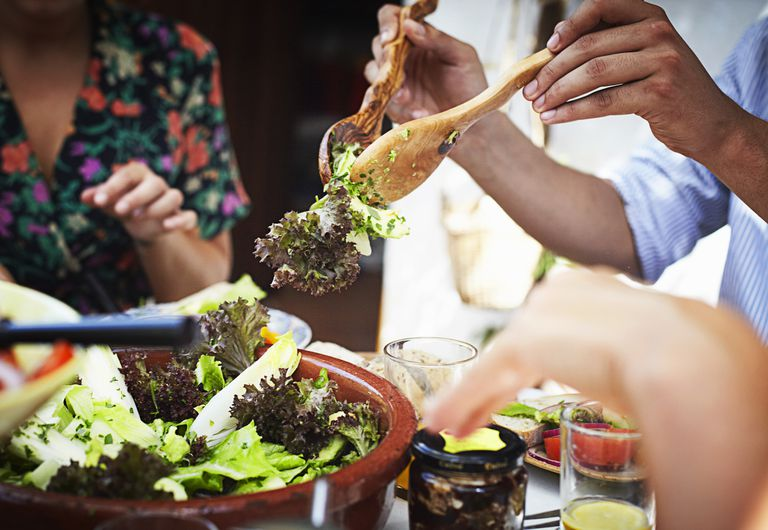 Man tossing spring mix salad while eating with friends