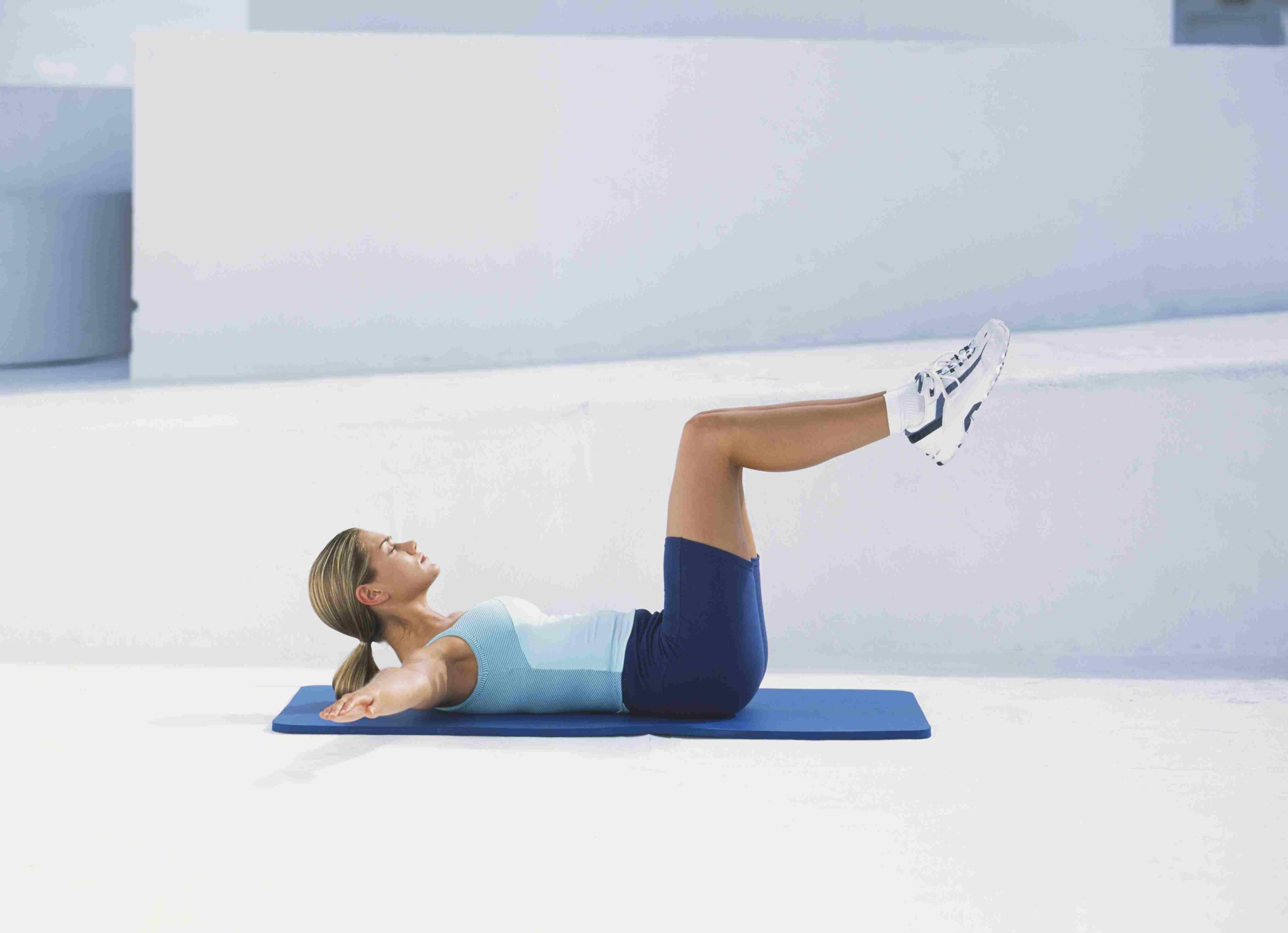 Mujer con camiseta sin mangas y pantalones cortos acostada boca arriba sobre una alfombra azul, con la cabeza levantada, los brazos estirados a los lados, las rodillas dobladas en ángulo recto con el cuerpo, vista lateral.