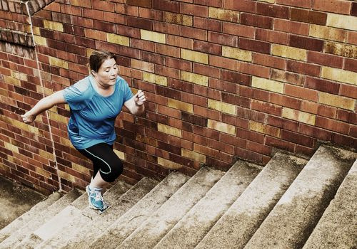 Overweight woman running up concrete stairs for exercise.
