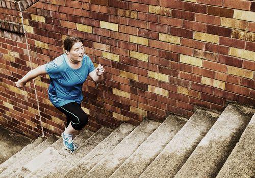 Mujer con sobrepeso corriendo escaleras de hormigón para hacer ejercicio.