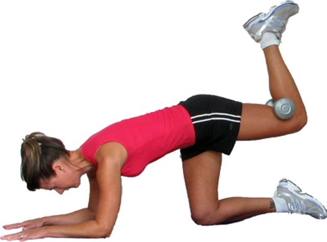 woman performing hip extensions with weights
