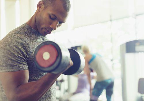 Hombre afroamericano sosteniendo pesas en el gimnasio
