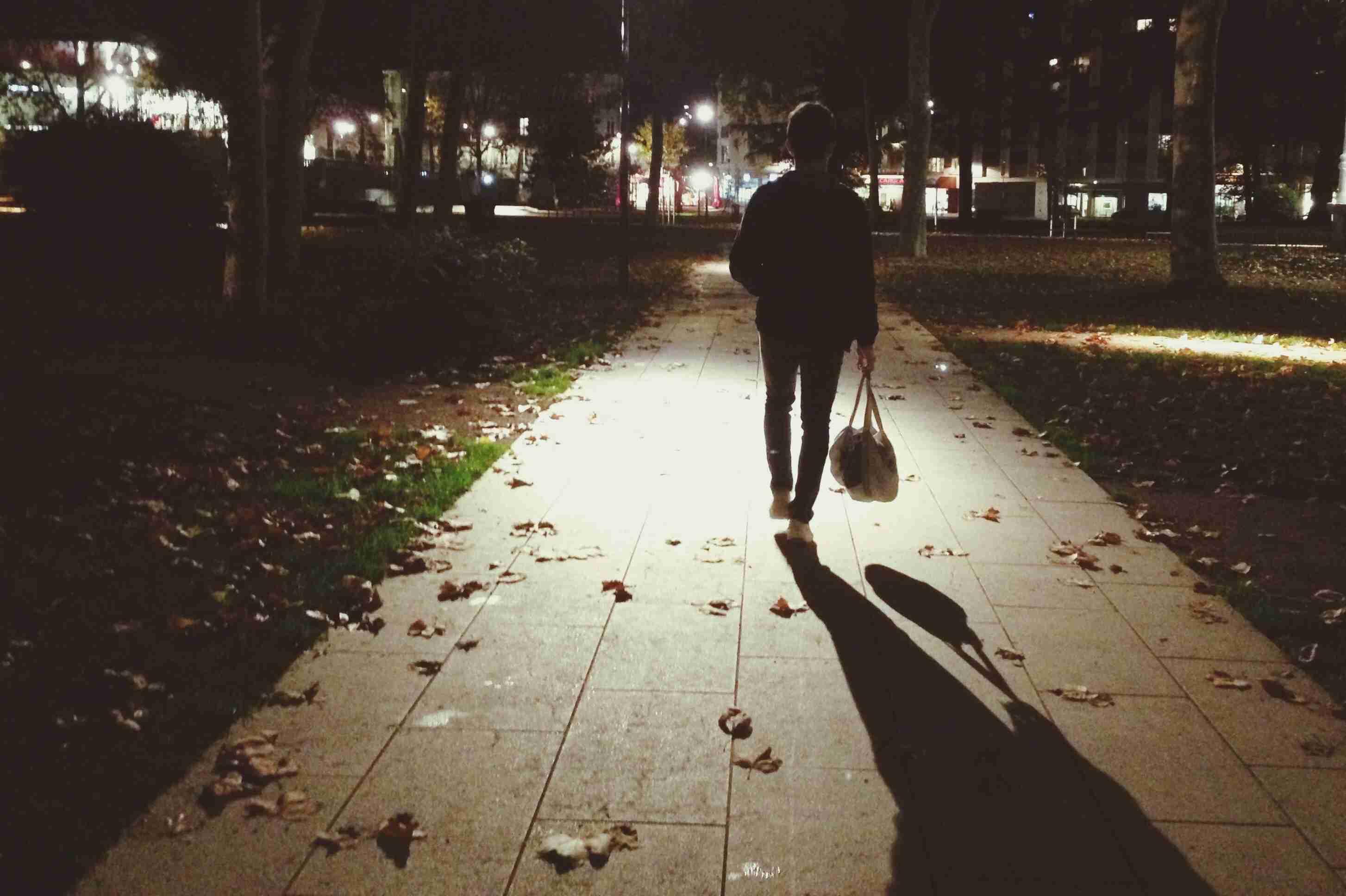 Woman walking on a sidewalk at night