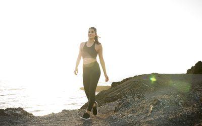 Young female runner walking on coastal dirt track, Las Palmas, Canary Islands, Spain