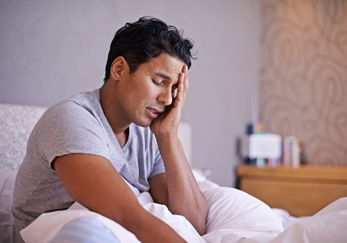 man with hangover holding head in bed