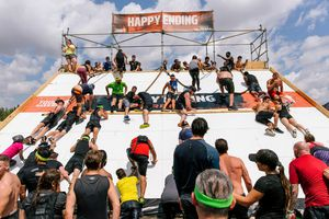 Tough Mudder participants climbing over a wall obstacle.