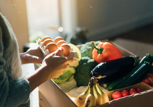 person holding eggs by vegetable box
