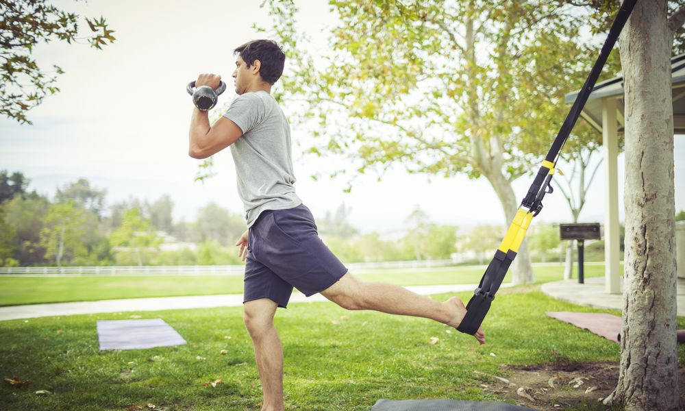 Young man exercising with trx in park