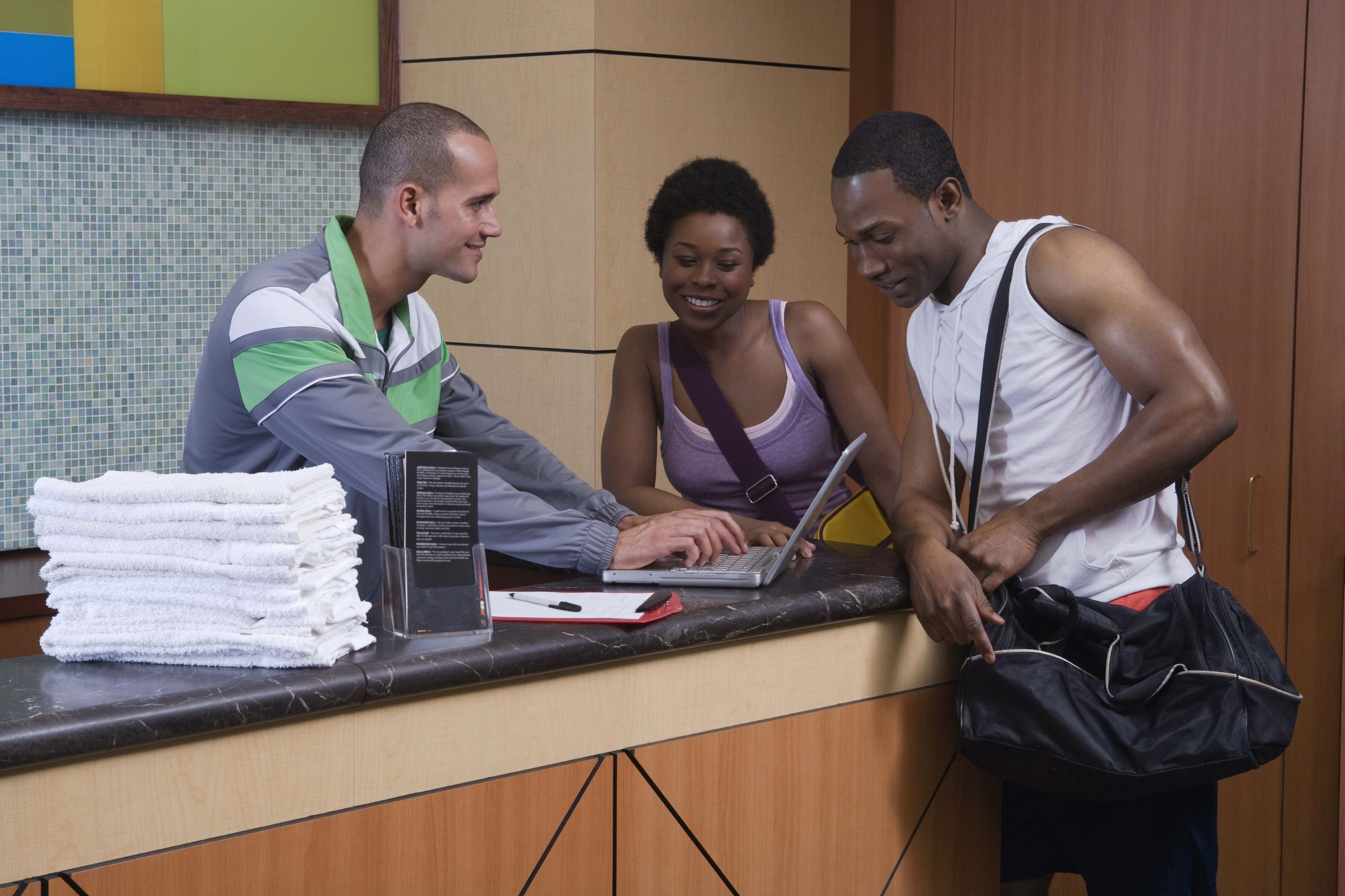 Gym employee helping couple at front desk 7de995aca0ba5