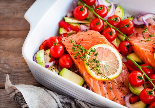 Una cazuela blanca con tomates cherry, salmón y verduras.