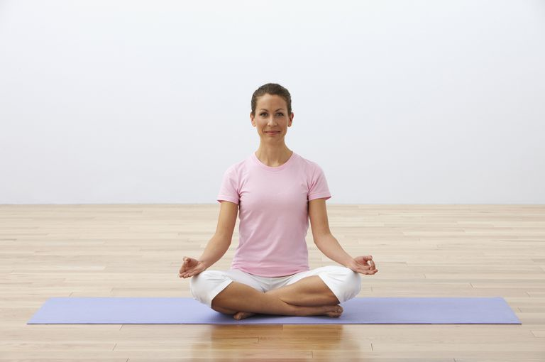 Woman sitting in easy pose on a yoga mat