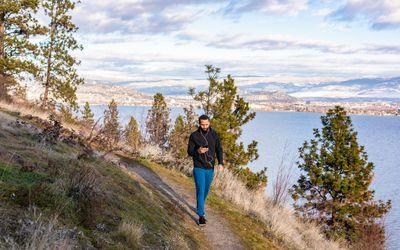 man walking on mountain trail checking phone